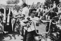 """""""Seventeenth Annual World's Largest Motorcycle Blessing, St. Christopher Shrine, Midlothian, Illinois"""" from The Bikeriders by © Danny Lyon  –"""