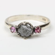 Dark gray rough diamond ring with pink sapphire side set gems in prongs setting with silver high polished finish band