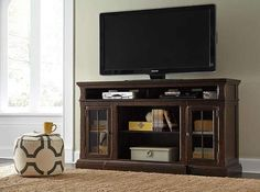 Roddinton TV Stand - The beauty of the Roddinton TV stand will immediately engage you. The slight breakfront shape is a rare find and an ideal fit among traditional and eclectic tastes. Soft black undertones highlight the warm finish. Multiple cubbies and glass-door enclosed shelves organize your audiovideo components and plenty of extras. Sold separately, an electric fireplace fits neatly in the center cubby.