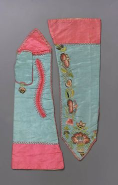 Pair of women's mitts, probably Italiy, 18th century. Blue silk trimmed with bright pink silk and embroidered with flowers worked in long and short stitch with pink, blue, green, and yellow silk and tarnished metal thread. Stained.