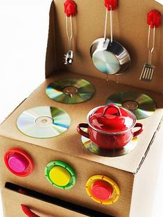 This cardboard stove will be a hot hit with your tot chef. What you'll need: 12x12x22-inch box, X-Acto knife, cutting mat, thick rope, 3 brads, 3 Play-Doh lids, 3 plastic caps, 4 CDs, 20x12-inch piece of cardboard, scissors, 3 adhesive-backed kitchen hooks Make it: Position flat box so flaps will be at right and left sides. Use an X-Acto knife and cutting mat to cut an oven door, as shown. Cut two 1-inch holes, about 6 inches apart, on oven door for handle; thr...