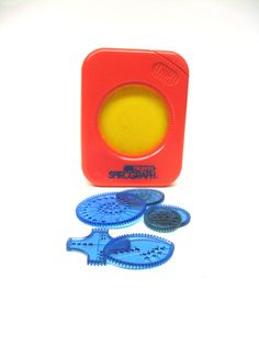 """I loved this when I was growing up! I brought this travel Spirograph with me everywhere. Do you remember how fun these were? This bit of personal history is a product of the 80s and has a bit of wear. 4 circle sizes, one """"x"""", and a football-shaped piece are all included. The original pens dried up years ago and I probably threw them out - you can still use any pen or pencil with these."""