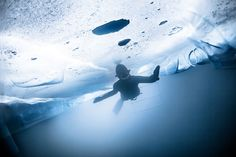 A freediver in Switzerland swims under a roof of ice in this National Geographic Your Shot Photo of the Day.