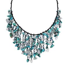 Adorn yourself with beautiful handmade jewelry from Thailand. This stunning cotton necklace features hand-beaded clusters of reconstructed turquoise, freshwater pearls, crystal and moonstone.
