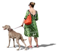 A woman in a green dress walking a dog
