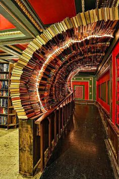 """Book Portals, The Last Bookstore, Los Angeles. The Labyrinth on the second floor of the Last Bookstore in downtown Los Angeles. The Labyrinth features a massive, chaotic, maze-like space housing more than 100,000 used books, all at $1 each. It features doors that lead nowhere, time-travel portholes looking into an artist's rendition of outer space, and """"secret passageways"""" leading into hidden book rooms."""