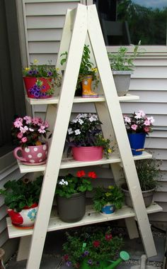 Flower ladder - paint old ladder, and add planks so that there is extra room for pots....good way to display my mint collection in a vertical way!