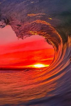 Flaming red sunset seen through the pike of a wave. Stunning! Beautiful wave and sky.
