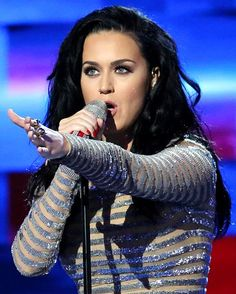 Katy Perry in performance, with her left arm raised