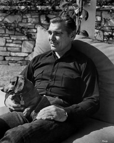 """Taking it easy at his San Fernando Valley home is Clark Gable, with his favorite dachshund pet, as he relaxes after a ride in the neighboring hills. Gable will do plenty of riding, too, on the screen in his latest picture, Metro-Goldwyn-Mayer's action drama of the early Texas, ""Lone Star."""