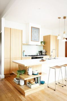Light-filled kitchen with pendant lights and light wood cabinetry