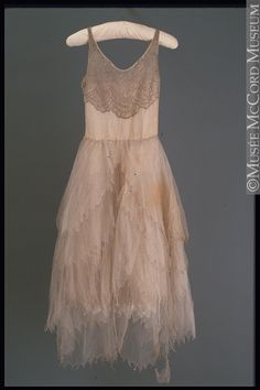 1929.  Norman Hartnell.  Beading on tulle. The simple camisole-style bodice pegs this as very youthful. Maturing it up could be accomplished with flutter sleeves. and overlay on the bodice.