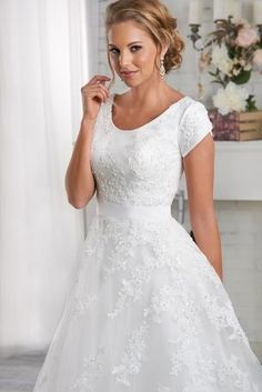 Totally Modest - Jane - Elegant lace placed asymmetrically creates movement through this modest gown. The lace drapes over the scoop neckline bodice and through the natural waistband and onto the A-line skirt and train. Fabrics: Lace, Tulle