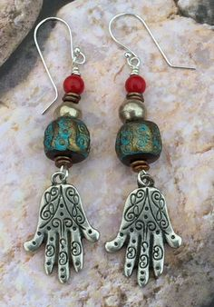 Boho embellished dangle earrings with artisan handmade beads and intricate silver hamsa hand charms. The handmade turquoise brown bronze artisan bohemian beads beautifully compliment the style of the earring. Petite Czech beads and African handmade silver add just the right about of subtle b