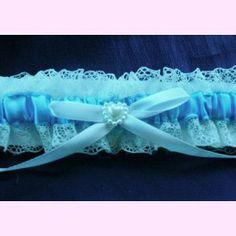 Liga de novia con cinta azul, adornada con lazo y detalle nacarado en forma de corazón. Tradición a un precio asequible.