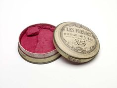 Part of Anna Pavlova's make-up tray, a circular box of Boots 'Les Fleurs' rouge de ville in bright pink (shade Rouge 24)    Production Date:  1920-1930  ID no:  31.81/15r  Location:  In Store
