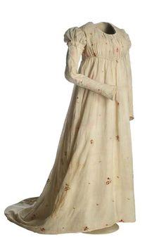 """Vestido """"camisa""""   Neoclasicismo, ca. 1805  Vestido en tafetán de algodón, en color blanco, guarnecido con una aplicación de bordado a punto de cadeneta que dibuja motivos florales polícromos salpicados por toda la superficie. Largo, con escote redondo en el delantero y talle debajo del pecho. La manga, muy larga, se abre en forma de embudo en la bocamanga.  MT000595"""