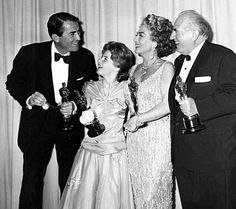 "Gregory Peck, holding pocket watch, jokes with, from left, Patty Duke, Joan Crawford and Ed Begley backstage at the Academy Awards at Santa Monica Civic Auditorium in Los Angeles, Ca., April 8, 1963.  Peck won best actor for ""To Kill a Mockingbird""; Duke won best supporting actress for ""The Miracle Worker""; Crawford accepted the Oscar for Anne Bancroft, who won best actress for ""The Miracle Worker""; and Begley won best supporting actor for ""Sweet Bird of Youth.""  (AP Photo)"