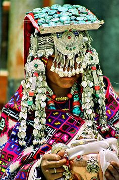 Picture of a person from Tibet.  They have very large pieces of jewelry on their head and even over their face.  The jewelry piece itself is not particular or significant but the colors that are used are.  The turquoise color is one that is very significant in the Tibetan culture.