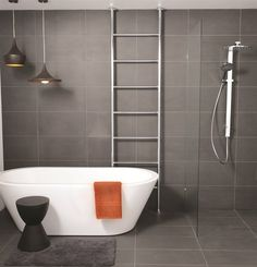 Love the grey tiles, metal ladder towel rail and freestanding bath