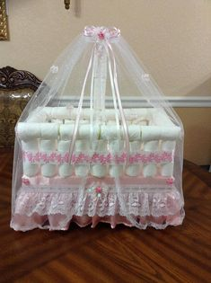 Elegant diaper crib perfect for a baby shower, both as a gift or even a centerpiece. It includes its baby doll inside, The top of the ornament is a mosquito net for baby. It is a beautiful imitation of a baby crib or for a baby shower. An original and elegant centerpiece or a nice