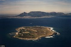 An aerial photograph of Robben Island with Cape Town in the background. Nelson Mandela spent 19 years imprisoned on the island. Nelson Mandela Pictures, Political Prisoners, Table Mountain, Let's Have Fun, Island Tour, Tour Operator, London, Day Tours, Cape Town