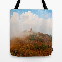 Castle ruin in fog and clouds Tote Bag A foggy morning in spring near my hometown. This is taken on my favorite place, I had to wait a while till I saw the ruin of Scharfenberg castle. The castle is build on the end of a row of rocks, on of them you see peeking out of the trees right of the ruin  Landscape, mountain, fog, clouds, spring, historical building,ruin, castle ruin, rock, trees, forest, Germany, sky
