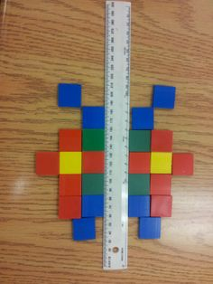 Grade 1 symmetry. With a partner, students take turns placing a square on either side of the ruler (the line of symmetry) to make a symmetrical design.