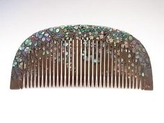 Earky Showa period comb.  Base colou is silver lacquer with black and gold lacquer with shall inlays.