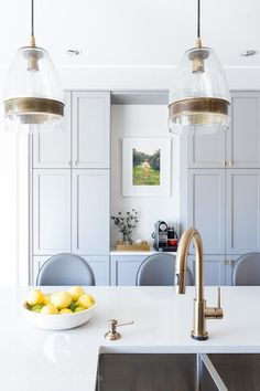 Beautiful kitchen features Crate & Barrel Morela Glass Pendant Lamps illuminating a white quartz waterfall center island fitted with a dual sink…