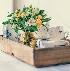 Misturar peças rústicas com outras delicadas é um recurso certeiro para uma decoração com personalidade: com lindas louças (podem ser desparceiradas) e um arranjo de flores, o caixote de frutas vira uma maneira diferente de dispor a mesa de chá