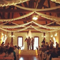 I really like the tulle and Christmas lights hanging from the ceiling, I'd like this in the reception space!