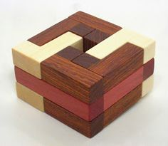 This beautiful puzzle was designed by Ken Irvine and made by Tom Lensch . It's called the Pink Ivory Ring; because one of the three woods us...