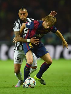 Ivan Rakitic of Barcelona holds off Arturo Vidal of Juventus during the UEFA Champions League Final between Juventus and FC Barcelona at Olympiastadion on June 6, 2015 in Berlin, Germany.