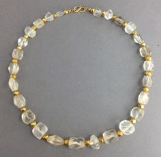 An ancient Roman necklace comprised of large clear crystal cornerless cube beads,  3rd -5th century AD, inter-spaced with modern gold beads. .
