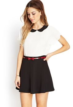 I like the red bow skirt. It adds a nice pop of color to the black and white outfit.