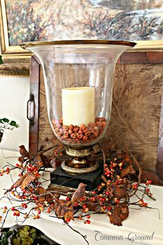 Autumn ~ decor ~ add candle and dried berries to hurricane globe, surround with fall foliage