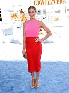 De 29-jarige actrice Brittany Snow droeg een enkellange jurk waarvan het bovenste gedeelte fel roze is en het onderste fel rood.It's all about the details getuige de goudkleurige accessoires, zachtroze lipstick en rood gelakte teennagels.