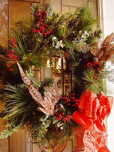 Mix classic elements, like winter berries and sprigs of greenery, with trendy accents, like textured feathers, to create a traditional yet updated wreath. Design by RMSer marykay.