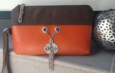 """Orange You Irish?""  A real leather look orange vinyl accented with a brown faux suede fabric.  The Celtic cross swings softly down the front.  Check out Bobbin My Thread on Facebok for more designs by Nena."