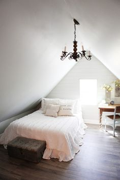White walls pair with hardwood floors, bringing in light that's reflected thanks to beautifully arched ceilings in this guest bedroom.