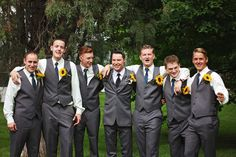 Groom + groomsmen in dark gray suits with sunflower boutonnieres for a rustic wedding {Alison D. Photography}