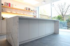 Handleless Matt Lacquer kitchen with Oak box shelves, Corian worktop and book matched Carrara Marble island.