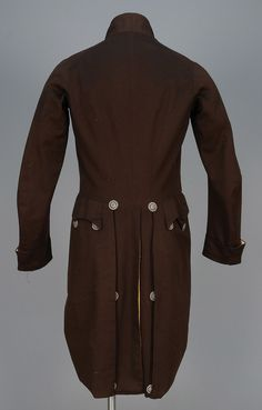 Early Regency men's fashion 1800s Back view of ENGLISH WOOL LIVERY COAT, 1790 - 1800.Brown broadcloth cutaway having cut steel buttons, corded false buttonholes, button decorated shaped pocket flaps, cuffs and deep back vent, silk lining. Ch-36, L-40.