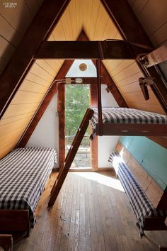 bunks in an A-frame loft with gingham coverlets (Interior Design Magazine)