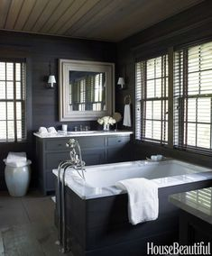 Sheathed in dark-stained pine with simple cabinetry, the master bathroom has the look of a rustic retreat in a Lake Martin, Alabama, house designed by Susan Ferrier.