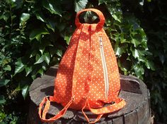 This is a little backpack made of orange polka dotted canvas. - zippered pocket at the front - zippered pocket on the back - closes with zipper on the side - adjustable strap - top carry handle - washable - handmade - unique - fashionable This bag is also ideal for childrens gym bag or lunch bag.  Dimensions: height 14/35cm, width 12/30cm, depth 3/8cm.  All of my items are ready for ship. The shipment is in registered package with tracking number via Airmail. Airmail takes appr...