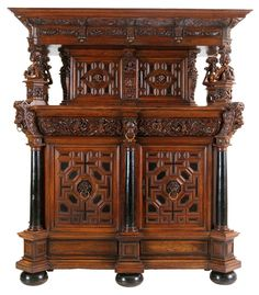 Cupboard. Walnut, partly ebonised, and ebony. Four panelled doors, one drawer. Flemish Renaissance, 17th century. Protruding stepped top carved with angel heads, foliage and birds, the frieze carved with fruit garlands, the stiles with male and female busts and the doors with male and female heads. The lower part with putti amidst foliage, the drawers with goat and fruit, flanked by detached columns stiles crowned by lion heads, the center stile with a 3/4 pilaster. Flattened bun feet.