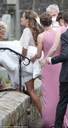Kim Sears gets help from her bridesmaids, dressed all in pink, as she enters the church...