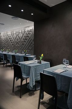 Separating the two dining areas in this modern restaurant,are dark sections of walls made from resin and cement in a dove grey and burnt coffee color that have a matte wax finish.